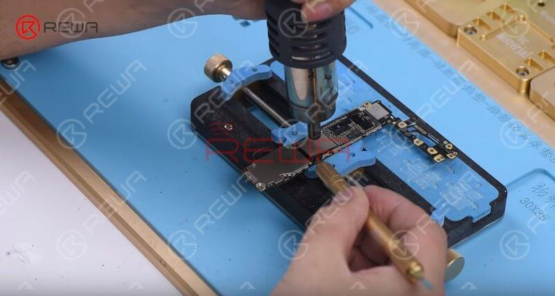 Attach the logic board to the PCB Holder. Heat with the QUICK 858D helical wind hot air gun at 280℃, air flow 5 and remove black adhesive around the NAND first.